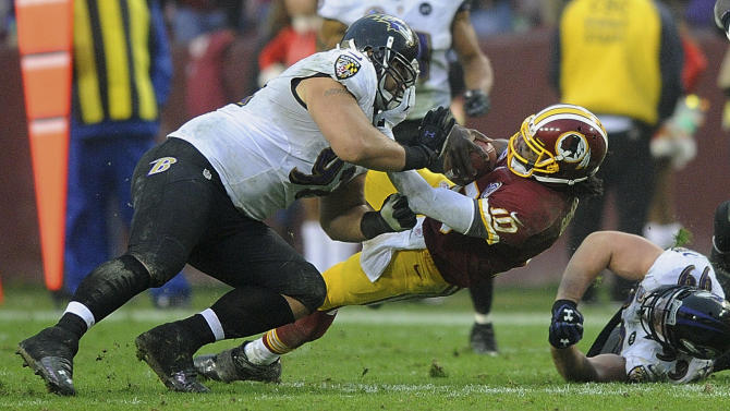 Washington Redskins quarterback Robert Griffin III is hit by Baltimore Ravens defensive end Haloti Ngata during the second half of an NFL football game in Landover, Md., Sunday, Dec. 9, 2012. (AP Photo/Nick Wass)