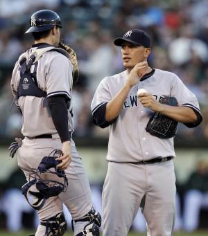 New York Yankees' Freddy Garcia, right, speaks with catcher Chris Stewart in the fourth inning of a baseball game against the Oakland Athletics, Thursday, July 19, 2012, in Oakland, Calif. (AP Photo/Ben Margot)