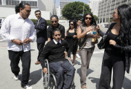 Luis Mijangos, seated, is surrounded by family members as he enters federal court to face computer hacking charges Thursday Sept. 1, 2011 in Los Angeles. Calling the crimes committed by Mijangos a form of cyber terrorism that inflicted great emotional distress on his victims, a judge sentenced Mijangos on Thursday to six years in prison for extorting sexually explicit photos from women and teenage girls whose computers he hacked. (AP Photo/Nick Ut)