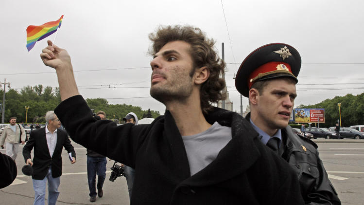 """FILE  - In this Saturday, May 16, 2009 file photo a gay rights activist is detained by a police officer  in Moscow, Russia. A controversial bill banning """"homosexual propaganda"""" will be submitted to Russia's lower house of parliament for the first of three hearings Tuesday, Jan. 22. 2013.(AP Photo/Alexander Zemlianichenko, file)"""