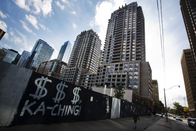 "A woman walks past graffiti which reads, ""KA-CHING"" near condominium buildings behind a lot of vacant land that is boarded up in Toronto in this September 21, 2012 file photo. It's looking like an unsettling spring in Canadian housing, a market that has proven far more even-keeled and less scary for investors in recent years than in the United States.   REUTERS/Mark Blinch/Files  (CANADA - Tags: BUSINESS CONSTRUCTION REAL ESTATE)"