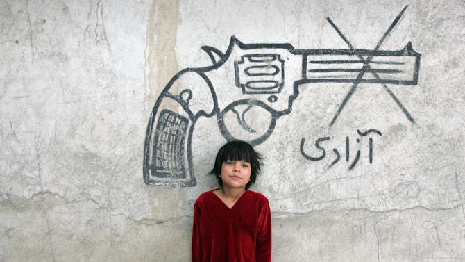 """An Afghan child poses for a photograph beneath graffiti of a pistol, with writing that reads, """"freedom,"""" in Kabul, Afghanistan, Sunday, Feb. 10, 2013. (AP Photo/Ahmad Nazar)"""