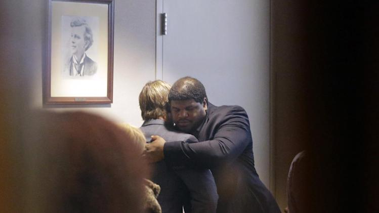 Former Dallas Cowboys NFL football player Josh Brent, right, hugs Dallas Cowboys linebacker Sean Lee in court after closing arguments in his intoxication manslaughter trial Tuesday, Jan. 21, 2014, in Dallas. The jury has begun deliberating in Brent's intoxication manslaughter trial after lawyers wrapped up their closing arguments Tuesday morning. Prosecutors accuse the former defensive tackle of drunkenly crashing his Mercedes near Dallas during a night out in December 2012, killing his good friend and teammate, Jerry Brown. (AP Photo/LM Otero)