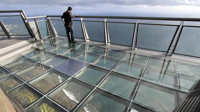 In this photo taken Oct. 31, 2012, a man visits the Portuguese Madeira Islands regional government's latest showpiece investment, a panoramic steel-and-glass viewing point perched on what claims to be Europe's highest cliff-top in Cabo Girao, Portugal. The price tag for the platform, parking lot and cafe was euro 2.5 million. That's a hefty outlay for a near-bankrupt archipelago of about 250,000 people which has euro 6.3 billion in public debt, needed a euro 1.5 billion bailout last year and has promised to be frugal. But development funds from the European Union, bankrolled by the continent's taxpayers, made it affordable by picking up euro 2 million of the tab. (AP Photo/Joana Sousa)