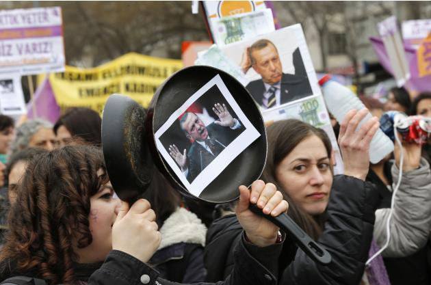 A woman raises frying pans with an attached portrait of Turkey's Prime Minister Erdogan on one of it, during an International Women's Day protest in Ankara