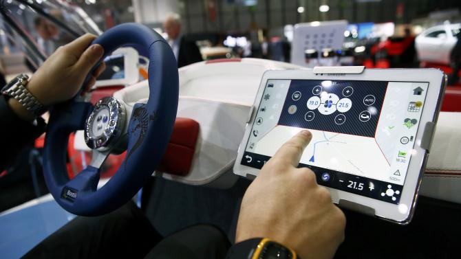 An employee sits inside a virtual reality connected car cockpit built by Segula Technologies during the first press day ahead of the 85th International Motor Show in Geneva