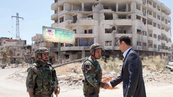 This image posted on the official Facebook page of the Syrian Presidency on Thursday, Aug. 1, 2013 purports to show Syrian President Bashar Assad shaking hands with a soldier during Syrian Arab Army day in Darya, Syria. Syrian state-run TV says Assad has visited a tense Damascus suburb to inspect his troops on the occasion of the country's Army Day. The visit on Thursday is Assad's first known public trip outside the capital, his seat of power, since he visited the Baba Amr district in the central city of Homs after troops seized it from rebels in March 2012. Daraya, just south of Damascus, was held by rebels for a long time and it took the army weeks of heavy fighting to regain control earlier this year. (AP Photo/Syrian Presidency via Facebook)
