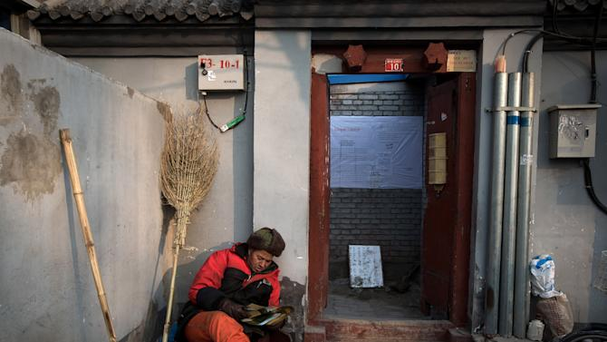 In this photo taken on Dec. 26, 2012, a street worker takes a rest near an entrance door of a Hutong home with a demolition notice on its wall near the historical Drum and Bell Tower in Beijing. The district government wants to demolish these dwellings, move their occupants to bigger apartments farther from the city center and redevelop a square in 18th century Qing Dynasty fashion. (AP Photo/Andy Wong)