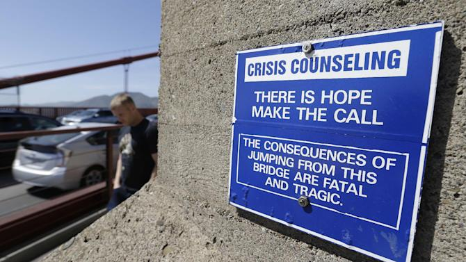 In this photo taken Tuesday, April 30, 2013 a sign is posted above a crisis counseling call box on the Golden Gate Bridge in San Francisco. About 1,500 people have plunged from the bridge, making it one of the world's favorite suicide spots. (AP Photo/Eric Risberg)