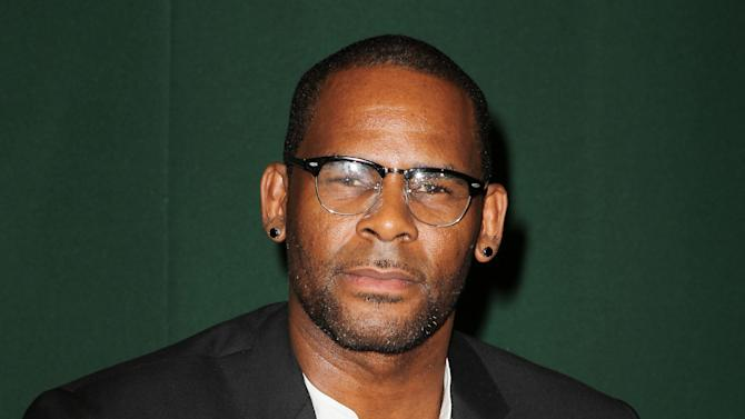 """FILE - This Aug. 10, 2012 photo originally released by Starpix shows R&B singer R. Kelly signing copies of his memoir, """"Soulacoaster: The Diary of Me,"""" at Barnes & Noble in New York. R. Kelly has been all about romance on his last two albums, but the self-proclaimed Pied Piper of R&B says he isn't going to abandon the raunch that helped make him famous. Kelly's recent """"Write Me Back"""" and 2010's """"Love Letter"""" was a departure of sorts for the singer-songwriter, whose hits include classics like """"Your Body's Calling.""""  Kelly described those acclaimed albums as a way of taking a break from his typical explicit material to try something new. (AP Photo/Starpix, Amanda Schwab, file)"""