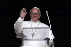 Pope Francis waves to the faithful as he appears at the window of his future private apartment in St. Peter's Square, during the Angelus prayer at the Vatican