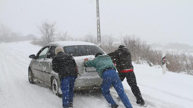 People push a car stranded by a heavy snowstorm on a road between Miskolc and Harsany, 155 kms northeast of Budapest, Hungary, Friday March 15 2013. Winter weather returning to Hungary with heavy snowfall, blizzards, ice and cold has left thousands without electricity, blocked access to several localities, forced traffic halts in major services and caused several accidents across the country.  (AP Photo/MTI, Janos Vajda)