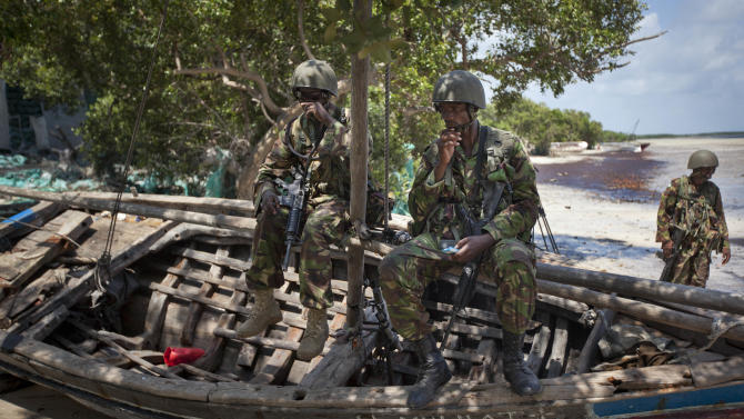FILE - In this Wednesday, Dec. 14, 2011 file photo, Kenyan army soldiers sit on a currently unused fishing boat on the white sand shore of the seaside town of Bur Garbo, Somalia. Kenya's military said Friday, Sept. 28, 2012 that its troops attacked Kismayo, the last remaining port city held by al-Qaida-linked al-Shabab insurgents in Somalia, during an overnight attack involving a beach landing. (AP Photo/Ben Curtis, File)
