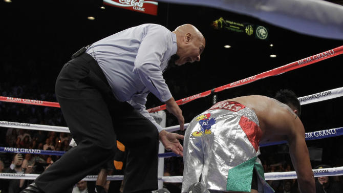 Referee Joe Cortez yells at Victor Ortiz after he was knocked down by Floyd Mayweather Jr. during their WBC welterweight title fight Saturday, Sept. 17, 2011, in Las Vegas. (AP Photo/Julie Jacobson)