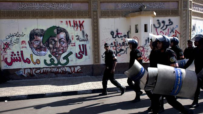 Egyptian riot policemen march past a mural on the wall of the presidential palace depicting president Mohammed Morsi, left, former military council ruler Hussain Tantawi, center and ousted president Mubarak with Arabic anti-Morsi graffiti, in Cairo, Egypt, Saturday, Dec. 8, 2012. Egypt's military warned Saturday of 'disastrous consequences' if the crisis that sent tens of thousands of protesters back into the streets is not resolved, signaling the army's return to an increasingly polarized and violent political scene. (AP Photo/Nasser Nasser)
