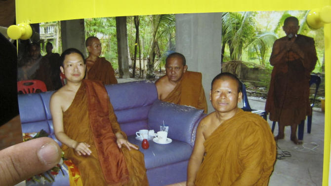 In this photo taken Monday, July 15, 2013, a photo of fugitive ex-monk Wirapol Sukphol, left, is shown by Songkran Artchariyasarp, a lawyer and Buddhist activist in Bangkok, Thailand. Now Wirapol is at the center of the biggest religious scandal the predominantly Buddhist country has seen in years. Critics say the case is an extreme example of a wider crisis in Thai Buddhism. The arrest warrant implicates Wirapol on three charges including statutory rape, embezzlement and online fraud to seek donations. He is also under investigation for money laundering, drug trafficking and manslaughter for a hit-and-run accident. Authorities are struggling to figure out how he amassed so much money. (AP Photo/Sakchai Lalit)