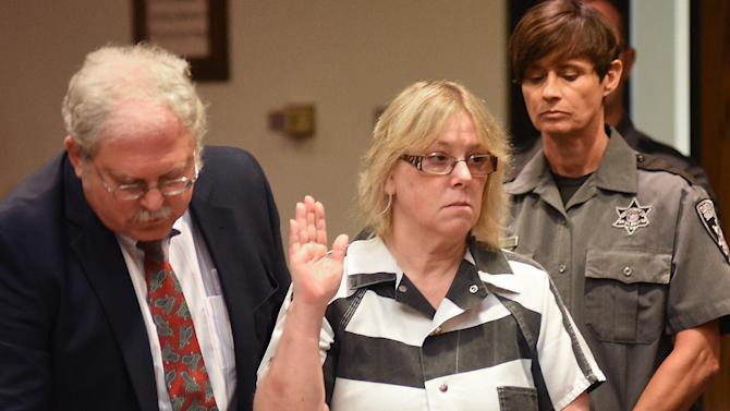 Joyce Mitchell raises her hand during a court appearance with her attorney Stephen Johnston on Tuesday July 28, 2015 in Plattsburgh, N.Y.  Mitchell, an instructor in the tailor shop at the Clinton Correctional Facility, pleaded guilty to charges of aiding two inmates convicted of murder by smuggling hacksaw blades and other tools to the pair, who broke out and spent three weeks on the run in June. She faces a sentence of 2 1/3 to 7 years in prison under terms of a plea deal with prosecutors.  (Rob Fountain/The Press-Republican via AP, Pool)