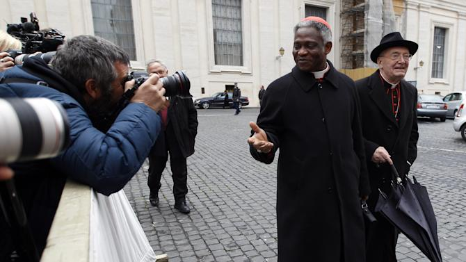 "Cardinal Peter Kodwo Appiah Turkson, center, is photographed by the media as he arrives for an afternoon meeting, at the Vatican, Friday, March 8, 2013. The Vatican says the conclave to elect a new pope will likely start in the first few days of next week. The Rev. Federico Lombardi told reporters that cardinals will vote Friday afternoon on the start date of the conclave but said it was ""likely"" they would choose Monday, Tuesday or Wednesday. The cardinals have been attending pre-conclave meetings to discuss the problems of the church and decide who among them is best suited to fix them as pope. (AP Photo/Alessandra Tarantino)"