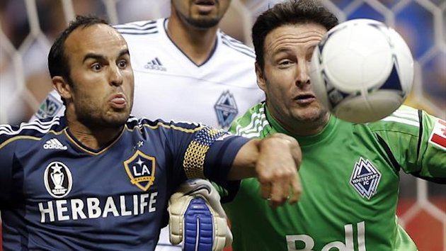Landon Donovan of the LA Galaxy in action against Vancouver Whitecaps goalkeeper Joe Cannon (Reuters)