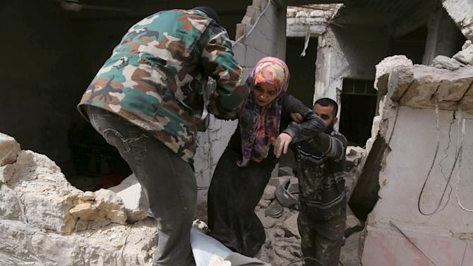 Residents help a woman amidst the rubble of her house after her family died at a site hit by what activists said was a barrel bomb dropped by warplanes operated by forces of Syria's President Assad in the Al-Sakhour neighbourhood of Aleppo