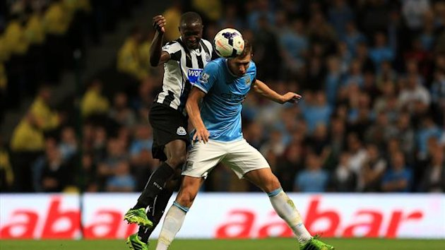 Manchester City's Edin Dzeko (right) and Newcastle United's Mapou Yanga-Mbiwa (left) battle for the ball (PA Photos)