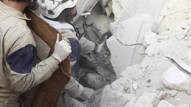 Civil defence members rescue a girl from under the rubble after airstrikes by pro-Syrian government forces in the rebel held al-Qaterji neighbourhood of Aleppo