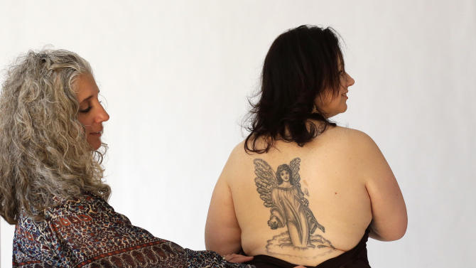 In this Sunday, Dec. 30, 2012 photo Stephanie Niewola, of Cranston, R.I., right, is directed by Paula McLaughlin, left, during a photo shoot for people with tattoos they had made in honor of those killed or injured during the Station Nightclub fire, in West Warwick, R.I., in February of 2003. Photos from the shoot are to be displayed in an exhibit held to honor those killed or injured in the blaze that took 100 lives. (AP Photo/Steven Senne)