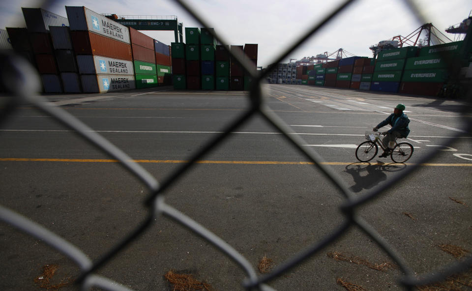 A worker pedals a bicycle at a container terminal in Tokyo, Wednesday, Jan. 25, 2012. Japan reported its first annual trade deficit since 1980 as it imported expensive energy to offset shortfalls caused by the devastating tsunami and manufacturers shifted production overseas to avoid the damage inflicted by the strong yen. (AP Photo/Junji Kurokawa)