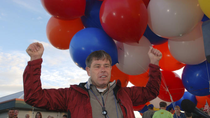FILE - In this July 5, 2008 file photo, Kent Couch describes the joy of his childhood fantasy of being able to fly by grabbing clusters of helium balloons prior to taking flight, in Bend, Ore. In 2008, Kent Couch made headlines by floating from Oregon to Idaho on a lawn chair hoisted into the clouds by party balloons. He's going to fly again, this time with a buddy sitting on a second lawn chair at his side. They are planning to take off July 14, 2012 from the parking lot of Couch's gas station and convenience store in Bend, Ore., the way he did in 2008 when he floated 235 miles to an Idaho farm field. Riding on a lawn chair attached to Couch's will be Fareed Lafta, an Iraqi adventurer and skydiver. Couch says he and Lafta plan to travel farther than on Couch's last trip going all the way to southwestern Montana, about 360 miles. (AP Photo/Jeff Barnard, File)
