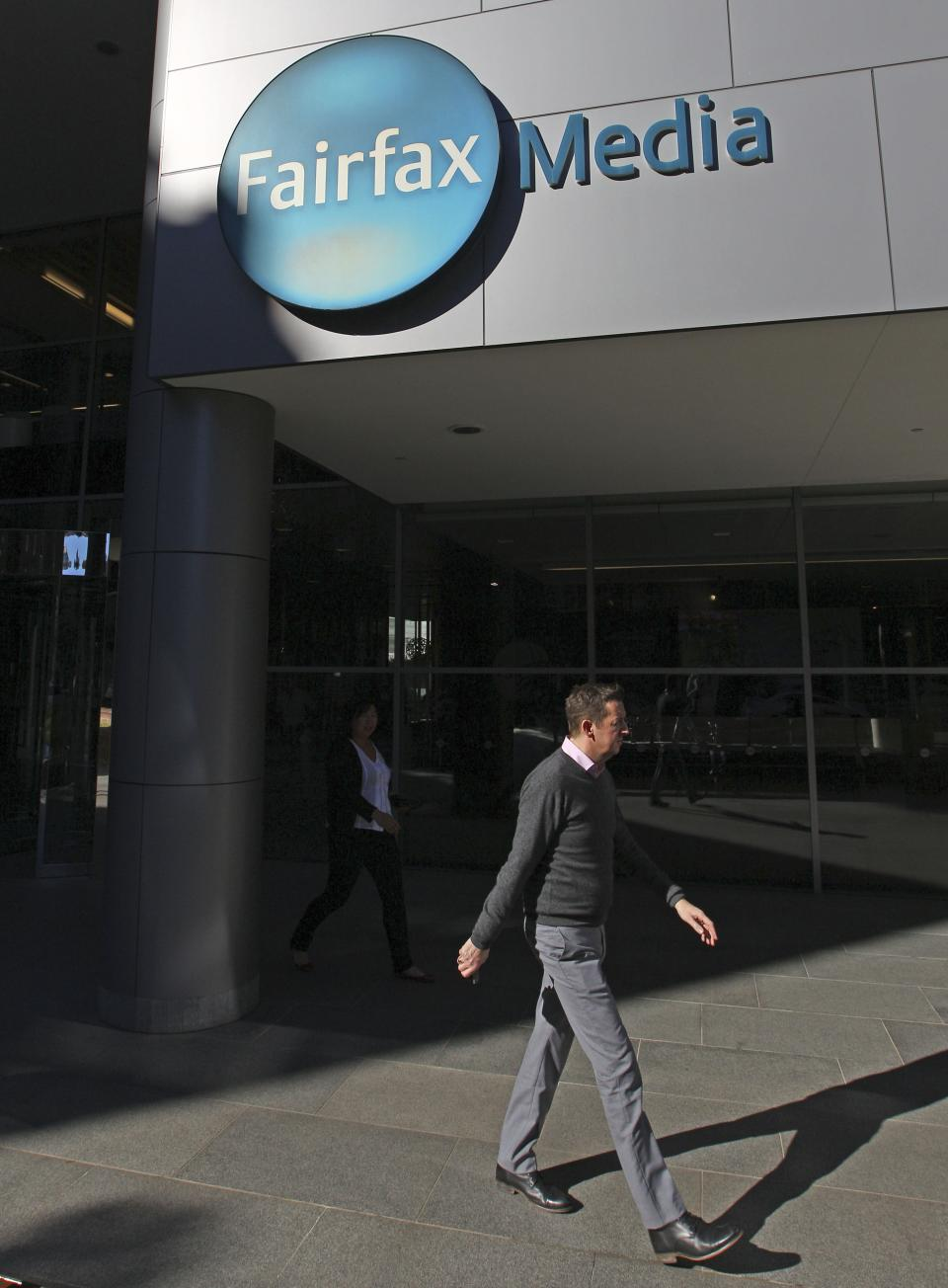 A man walks past the Fairfax headquarters in Sydney, Monday, June 18, 2012. Australian publisher Fairfax Media Ltd. said Monday it will shed 1,900 jobs over three years and erect pay walls for two flagship newspapers as readers increasingly move online. (AP Photo/Rick Rycroft)