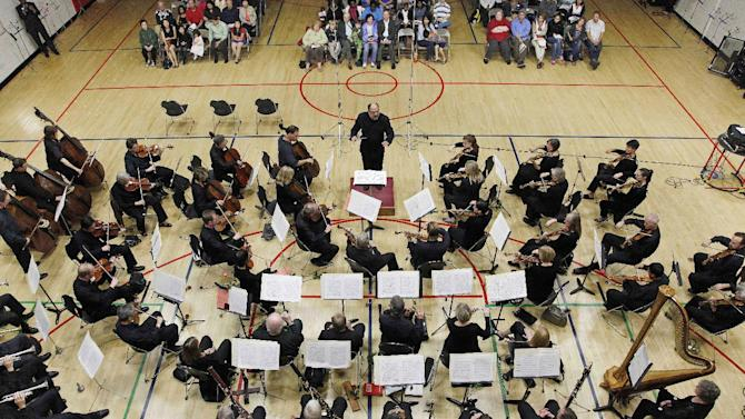 In this photo taken Monday, Sept. 24, 2012, the Musicians of the Minnesota Orchestra perform under the conducting of Kenneth Freed in a gymnasium at the ACME Concert, a free event at the North Community YMCA,  in Minneapolis. The Minnesota Orchestra was called the world's greatest not long ago, welcome recognition for musicians outside a top cultural center. Now its members are locked out of Orchestra Hall, stuck in the same kind of labor-management battle recently afflicting teachers and football referees. (AP Photo/Stacy Bengs)