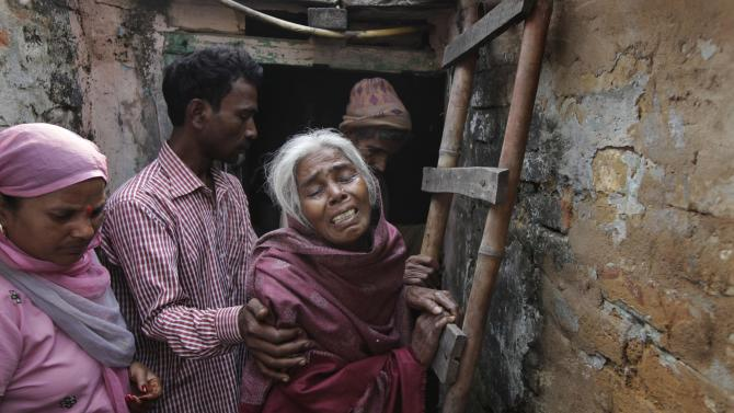 Unidentified relatives of Ram Singh, the man accused of driving the bus on which the 23-year-old student was gang raped in December 2012, walk with Singh's mother outside the family's home in New Delhi, India, Monday, March 11, 2013. Indian police confirmed that Ram Singh, one of the men on trial for his alleged involvement in the gang rape and fatal beating of a woman aboard a New Delhi bus committed suicide in an Indian jail Monday, but his lawyer and family allege he was killed.(AP Photo/Manish Swarup) INDIA OUT