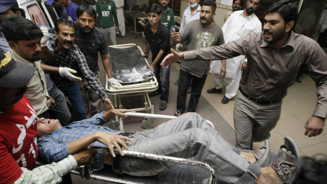 People rush an injured man to an emergency ward of a local hospital in Karachi, Pakistan  on Wednesday, Nov. 21, 2012. Two bombs exploded outside a Shiite mosque in the southern city of Karachi, killing scores of people and wounding others in a suicide attack, police official said. (AP Photo/Fareed Khan)