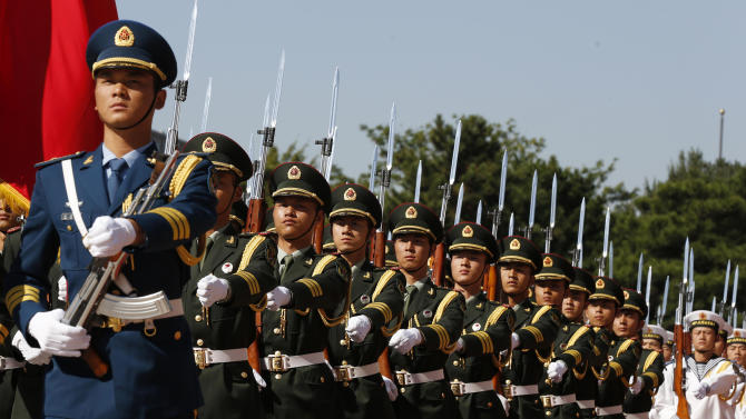 FILE - In this Tuesday, Sept. 18, 2012 file photo, Chinese military troops march before U.S. Defense Secretary Leon Panetta arrives at the Bayi Building in Beijing, China. The phrases to describe some of the looming foreign policy challenges for U.S. President Barack Obama didn't even exist when he took the oath of office the first time: the Arab Spring, the Fordo Facility housing Iran's underground uranium enrichment labs, the stealth power of new viruses bearing names such as Stuxnet and Flame in the shadow world of cyber-sabotage. Obama's re-election averts the immediate prospect of the United States designating China a currency manipulator, which Romney had promised to do on his first day in office. That would have been a setback to relations and could even have triggered a trade war between the world's two biggest economies.(AP Photo/Larry Downing, Pool, File)
