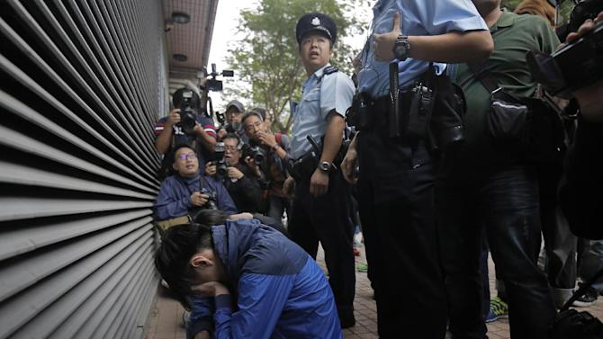 Two men are arrested by policemen after throwing eggs at prominent Hong Kong student protest leader Joshua Wong outside a court in Hong Kong Thursday, Nov. 27, 2014. Two men allegedly threw eggs at Wong and his lawyer as they were leaving court on Thursday. Wong and other democracy protesters were arrested the day before during a police operation to remove barricades from a protest camp in the unruly Mong Kok district. Wong was given bail and his case adjourned until January 14. (AP Photo/Vincent Yu)