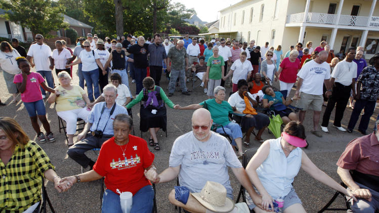 About 150 Crystal Springs, Miss., residents gather at the town square for a prayer rally in support of racial reconciliation Monday, July 30, 2012 following the actions of some congregants at the First Baptist Church which prevented a black couple from getting married there. (AP Photo/Rogelio V. Solis)