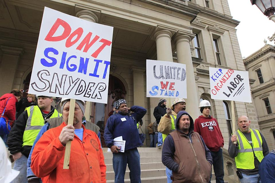 Union workers hold up a signs during a rally outside the Capitol in Lansing, Mich., Thursday, Dec. 6, 2012 as Senate Republicans introduced right-to-work legislation in the waning days of the legislative session.  (AP Photo/Carlos Osorio)