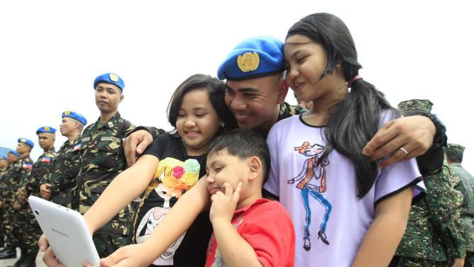 A member of the armed forces of the Philippines contingent takes a photo with his family during a sending-off ceremony in Pasay city