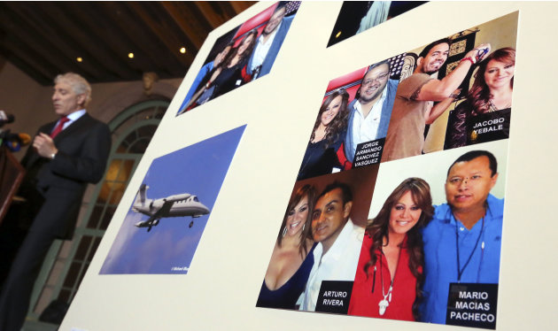A poster showing pictures of Jenni Rivera with four of her associates, all killed in a plane crash in Mexico in December, is displayed during a news conference where attorney Paul Kiesel, left, announ