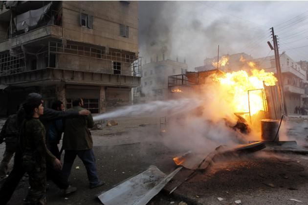 Residents try to put out a fire after what activists said was shelling from forces loyal to president Bashar Al-Assad on a fuel vendor in Al-Shaar area in Aleppo