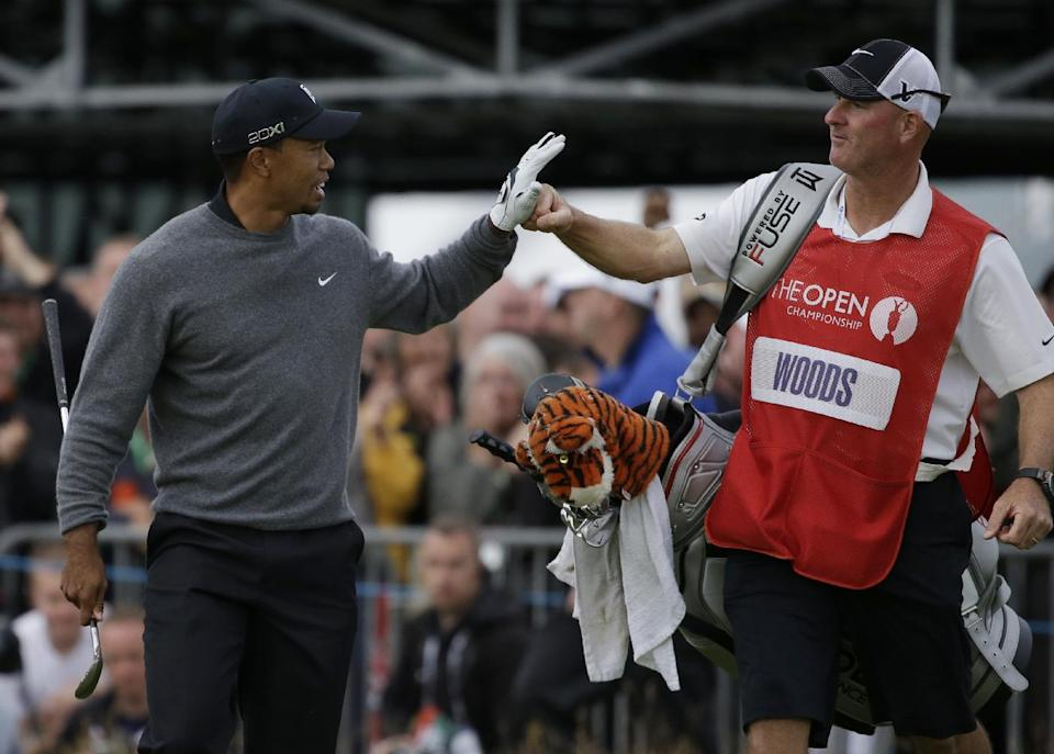Tiger Woods of the United States celebrates a birdie on the 18th hole with his caddie Joe LaCava at Royal Lytham & St Annes golf club during the second round of the British Open Golf Championship, Lytham St Annes, England, Friday, July 20, 2012. (AP Photo/Chris Carlson)