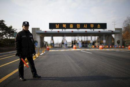 A South Korean security guard stands guard on an empty road which leads to the Kaesong Industrial Complex (KIC) at the South's CIQ, in Paju