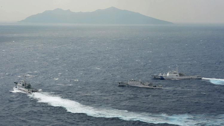 Japan Coast Guard vessels sail along with Chinese surveillance ship Haijian No. 66, center, near disputed islands called Senkaku in Japan and Diaoyu in China, seen in background, in the East China Sea, on Monday, Sept. 24, 2012. (AP Photo/Kyodo News) JAPAN OUT, MANDATORY CREDIT, NO LICENSING IN CHINA, HONG KONG, JAPAN, SOUTH KOREA AND FRANCE