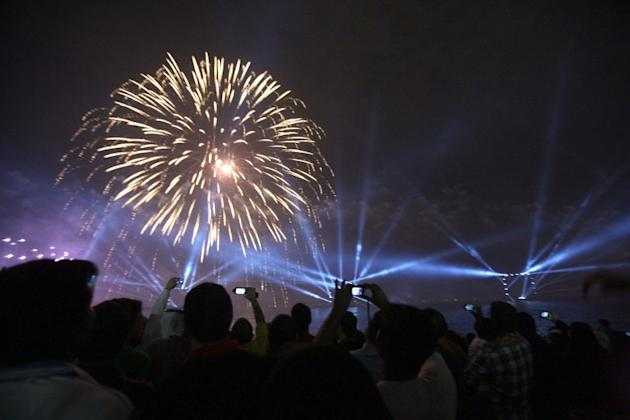 Kuwaitis take photographs as fireworks light the sky near the Kuwait Towers during celebrations marking the Gulf state's 50th anniversary of its constitution, in Kuwait City on November 10, 2012.  Kuw