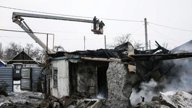 Repairmen work to repair the electricity network after what locals say was a night shelling in Donetsk
