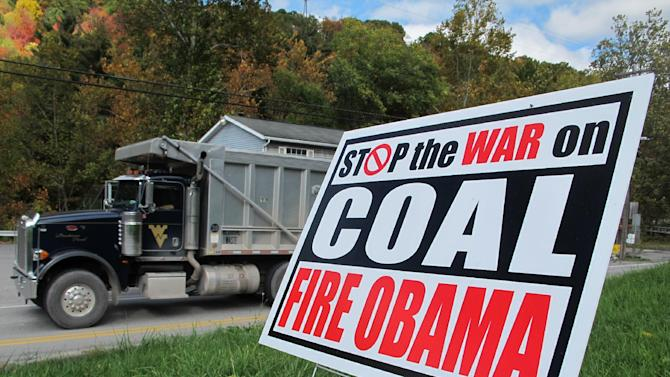 """A truck passes a political sign in a yard in Dellslow, W.Va., on Oct. 16, 2012. Rhetoric about the administration's alleged """"war on coal"""" has come to dominate conversation this campaign season.  Once, coal miners were literally at war with their employers. Today, their descendants are allies in a rhetorical war playing out across eastern Kentucky, southwestern Virginia and all of West Virginia. The message: They now face a common enemy _ the federal government, especially the president and the Environmental Protection Agency. (AP Photo/Vicki Smith)"""
