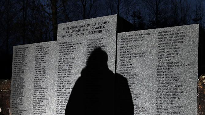 The shadow of a member of the public is seen looking at the main memorial stone in memory of the victims of Pan Am flight 103 bombing, in the garden of remembrance at Dryfesdale Cemetery, near Lockerbie, Scotland. Saturday Dec. 21, 2013. Pan Am flight 103 was blown apart above the Scottish border town of Lockerbie on Dec. 21, 1988. All 269 passengers and crew on the flight and 11 people on the ground were killed in the bombing. (AP Photo/Scott Heppell).