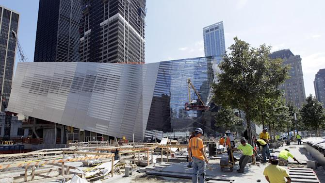 The National September 11 Memorial and Museum is seen in the background as workers put final touches on the World Trade Center Memorial, Wednesday, Aug. 17, 2011 in New York.  (AP Photo/Mary Altaffer)