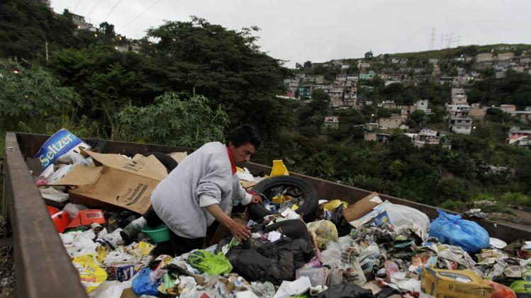 File photo of a man searching for food in a garbage dump at a low-income neighbourhood in Tegucigalpa