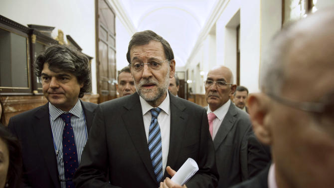 Spain's Prime Minister Mariano Rajoy leaves after a control session at the Spanish Parliament, in Madrid, Wednesday, June 13, 2012. The interest rate Spain would have to pay to raise money on the world's bond markets continued to rise Wednesday amid worries that a planned bank bailout might not be enough to save the country from needing an overall financial rescue. (AP Photo/Daniel Ochoa de Olza)